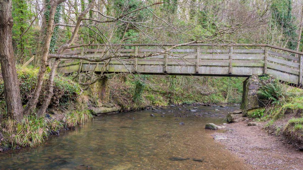 A wooden bridge spans Wepre Brook