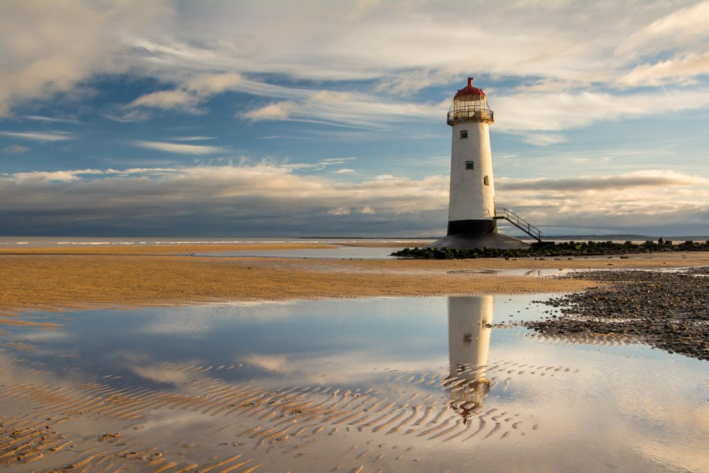 A reflection of the Point of Ayr Lighthouse in a tide pool