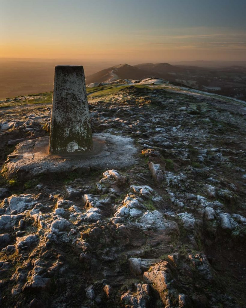 The Worcestershire Beacon trigpoint photographed during sunrise